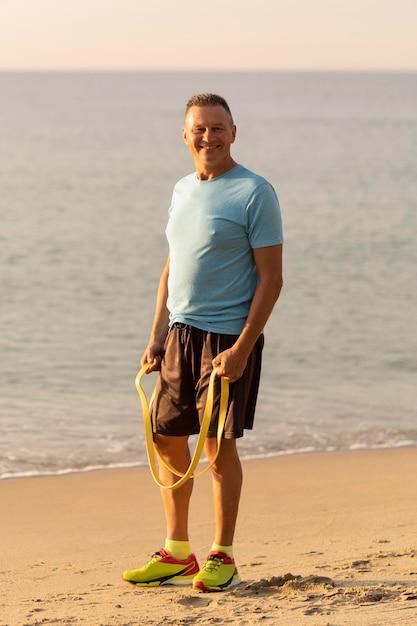 Uomo anziano sorridente con corda elastica sulla spiaggia Foto Gratuite