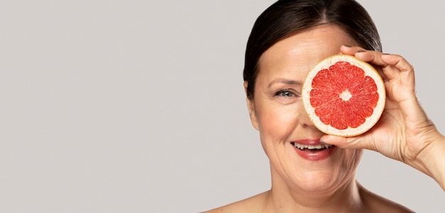 Смайлик старшая женщина закрыла глаз половиной грейпфрута Бесплатные Фотографии