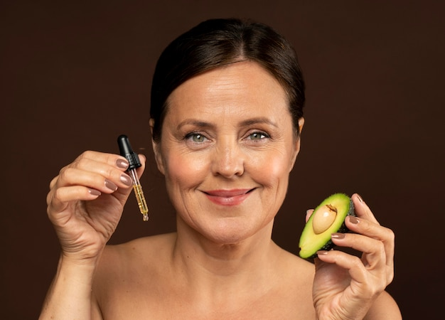 Смайлик старшая женщина держит половину авокадо с сывороткой Бесплатные Фотографии