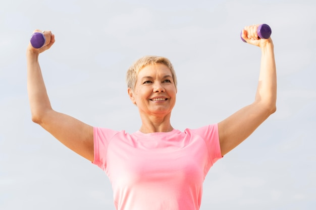 Smiley elder woman holding up weights while working out Free Photo