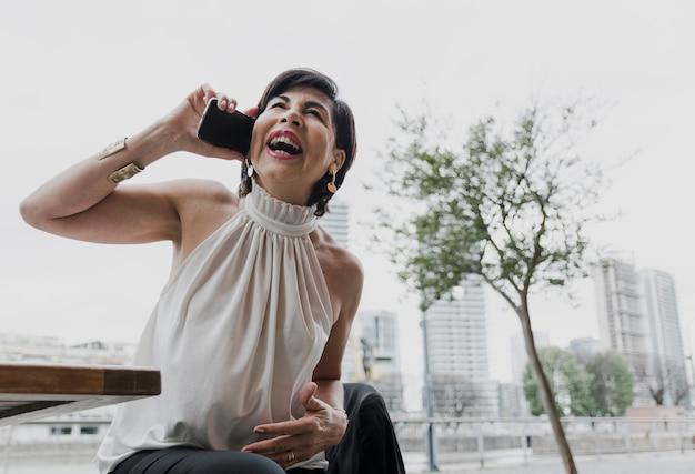 Smiley elder woman talking on the phone Free Photo