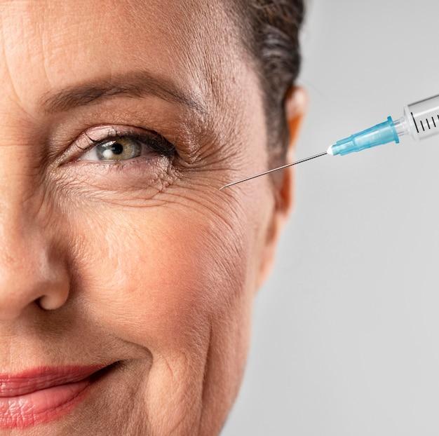 Donna anziana di smiley utilizzando l'iniezione per le rughe degli occhi Foto Gratuite