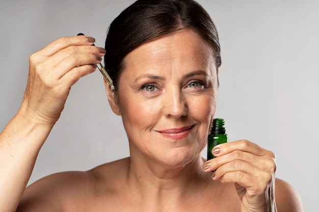 Smiley elder woman using serum on her face Free Photo