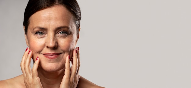 Smiley elder woman with make-up on posing with hands on face and copy space Premium Photo