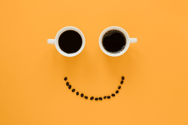 Smiley face of coffee cups and beans Premium Photo