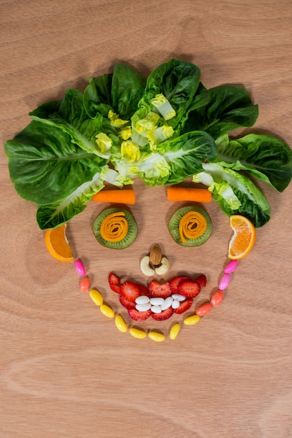 Smiley Face Made Of Confectionary And Vegetables Photo