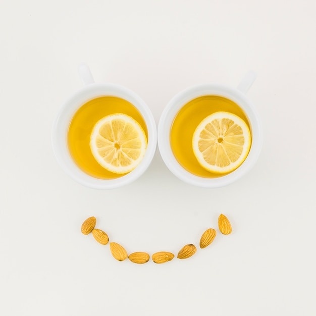 Smiley face made with lemon tea cup and almonds isolated on white background Free Photo