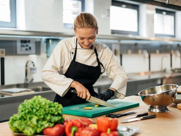キッチンで野菜を切るスマイリー女性シェフ Premium写真