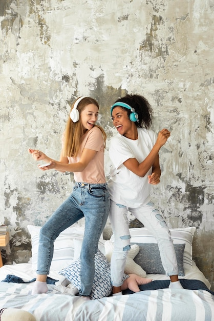 Smiley female friends dancing on bed while listening to music on headphones Free Photo