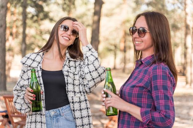 屋外でビールを飲むスマイリー女友達 無料写真