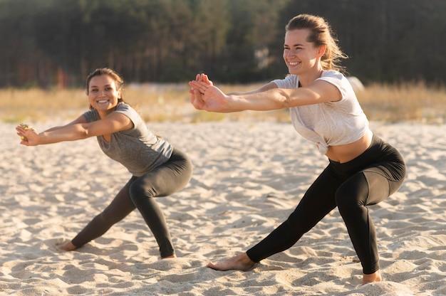 ビーチで運動するスマイリー女友達 無料写真