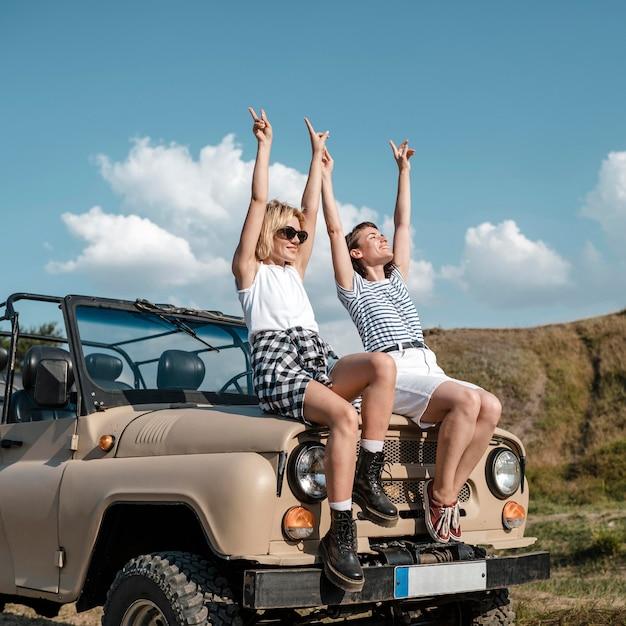 Amici femminili di smiley che hanno divertimento durante il viaggio in auto Foto Gratuite