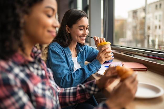 Улыбающиеся подруги обедают вместе Бесплатные Фотографии
