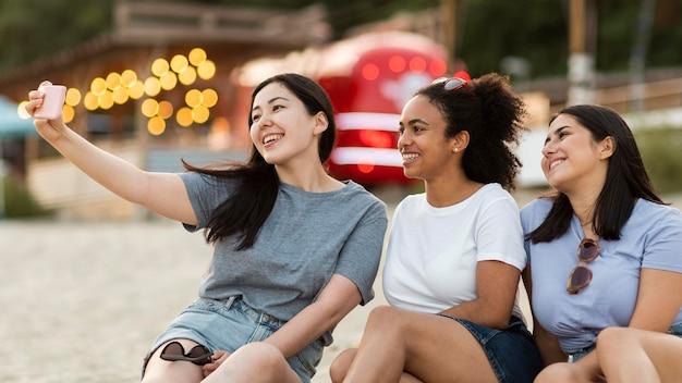 Улыбающиеся подруги сидят на пляже и делают селфи Бесплатные Фотографии