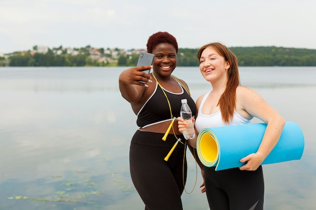 Smiley female friends taking selfie outdoors while exercising Free Photo