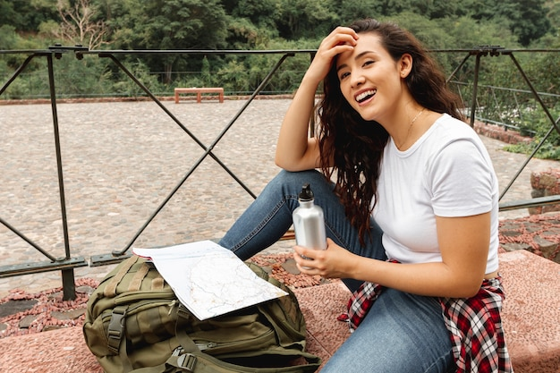 Smiley female traveling stop to hydrate Free Photo