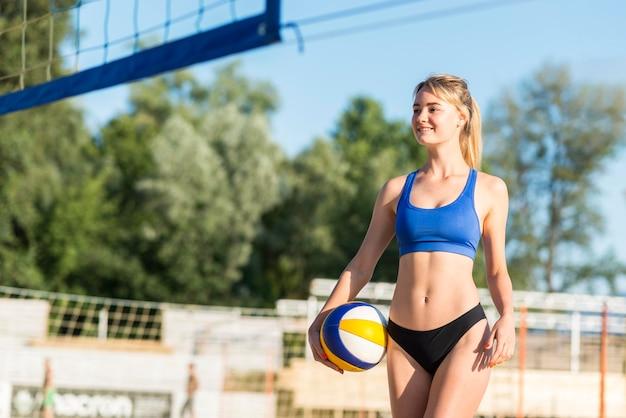 Giocatore di pallavolo femminile di smiley sulla sfera della holding della spiaggia Foto Gratuite