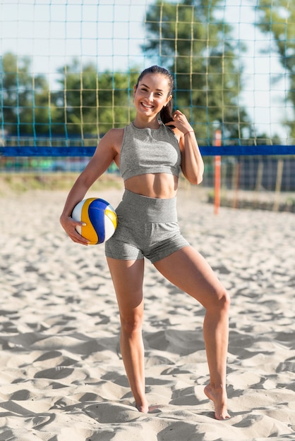 Giocatore di pallavolo femminile smiley sulla spiaggia in posa con la palla Foto Gratuite
