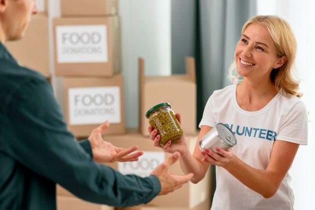 Volontario femminile di smiley che aiuta la persona bisognosa con disposizioni Foto Gratuite