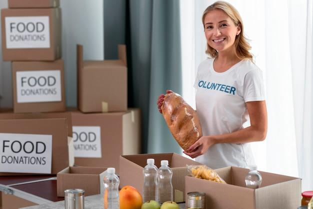 Смайлик женщина-волонтер помогает с пожертвованиями на еду Бесплатные Фотографии