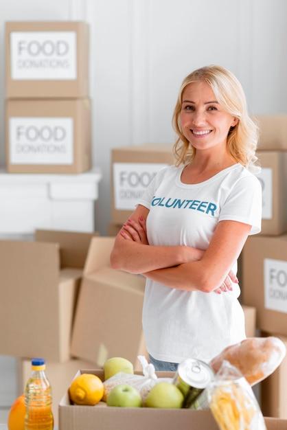 Смайлик-волонтер-женщина позирует рядом с пожертвованиями на еду Бесплатные Фотографии