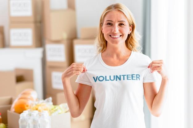 Смайлик-волонтер позирует, показывая футболку Premium Фотографии