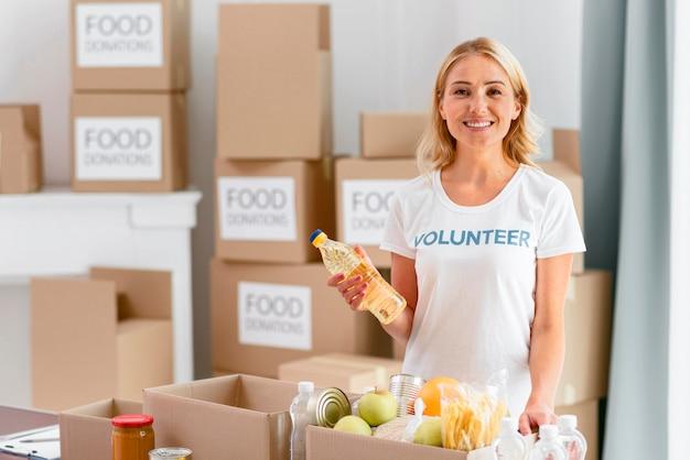 Смайлик-волонтер готовит коробку с едой для пожертвования Бесплатные Фотографии
