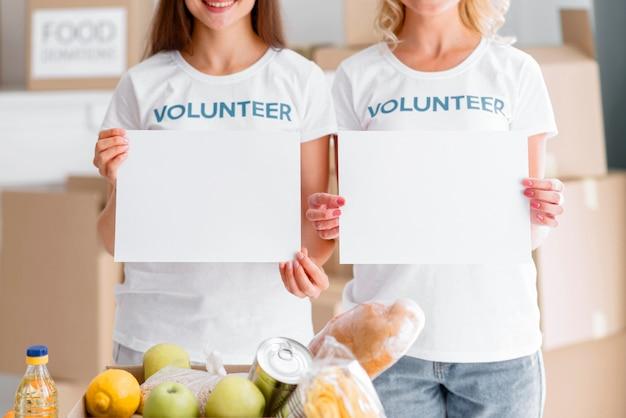 Volontari femminili di smiley in posa con cartelli vuoti e donazioni di cibo Foto Gratuite