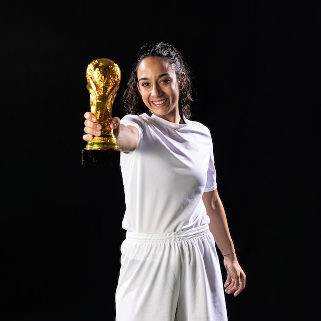 Smiley footballer holding world cup Free Photo