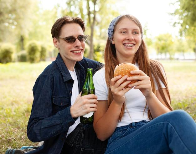 ビールとハンバーガーと公園でスマイリーの友達 無料写真