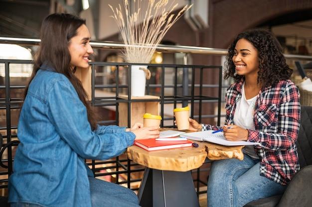 Улыбающиеся друзья вместе делают домашнее задание в кафе Premium Фотографии