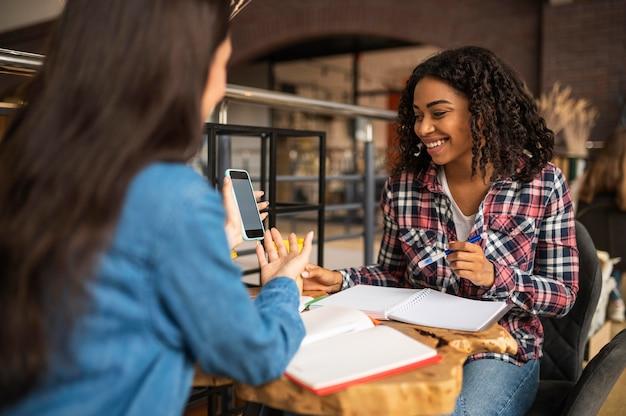 Улыбающиеся друзья делают домашнее задание с помощью смартфона в кафе Premium Фотографии