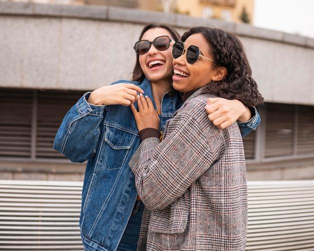 Улыбающиеся друзья веселятся вместе на открытом воздухе Бесплатные Фотографии