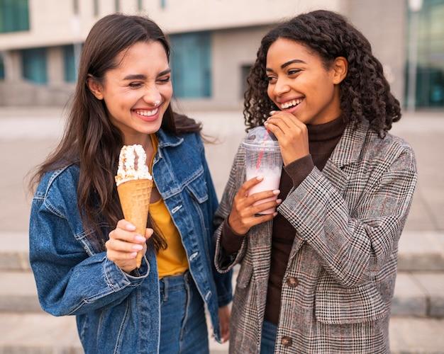 Улыбающиеся друзья пьют мороженое и молочные коктейли на улице Бесплатные Фотографии