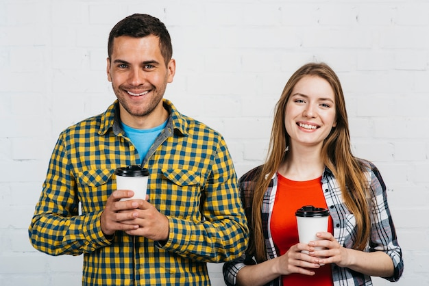 Smiley friends holding their cup of coffee Free Photo