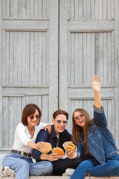 ハンバーガーを持っている屋外のスマイリー友達 無料写真