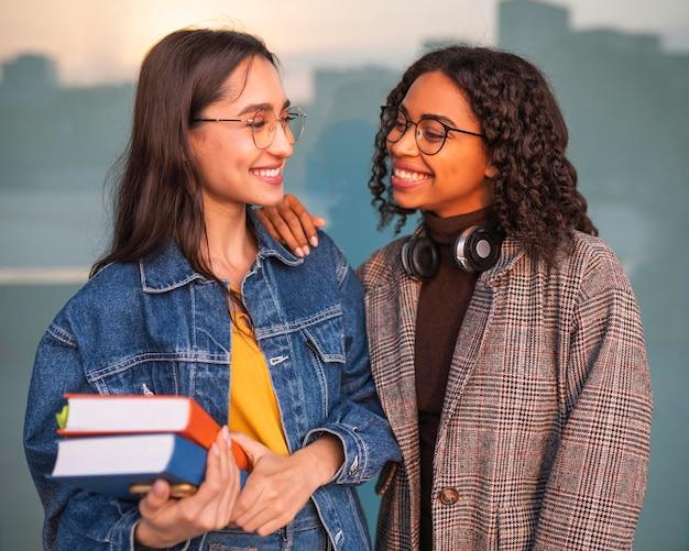 Amici di smiley in posa insieme a libri e cuffie Foto Gratuite