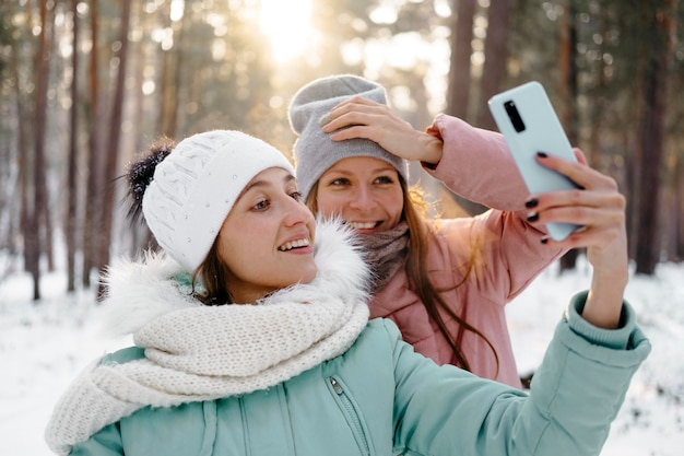 冬に屋外で自分撮りをしている笑顔の友達 無料写真