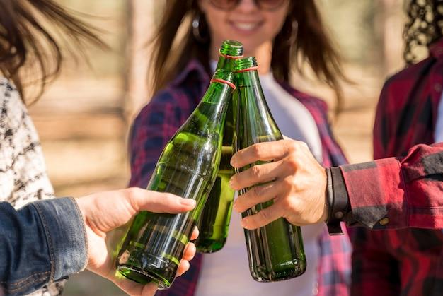屋外でビール瓶で乾杯するスマイリーの友達 無料写真