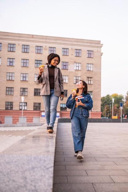 Amici di smiley con libri e caffè all'aperto Foto Gratuite