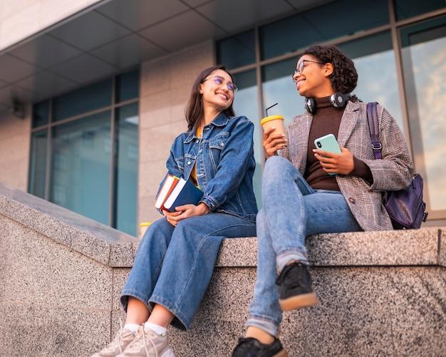 Amici di smiley con i libri che mangiano caffè insieme Foto Gratuite