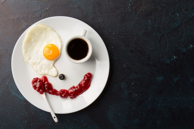Smiley from fried egg and coffee cup Free Photo