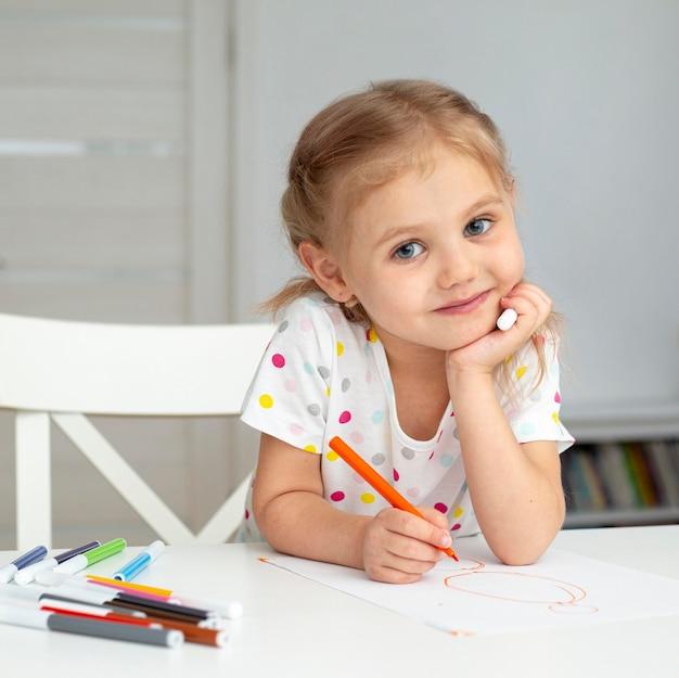 Улыбающаяся девушка дома рисует Premium Фотографии