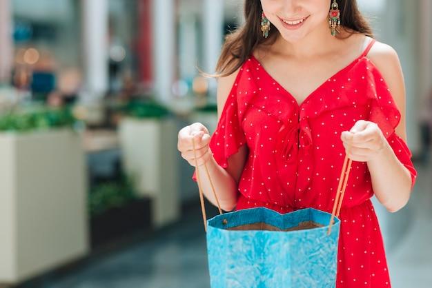 Smiley girl checking shopping bag Free Photo