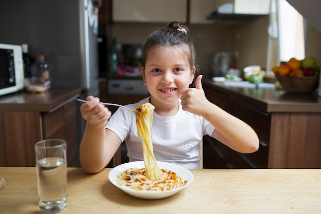 Smiley girl having pasta at lunch Free Photo