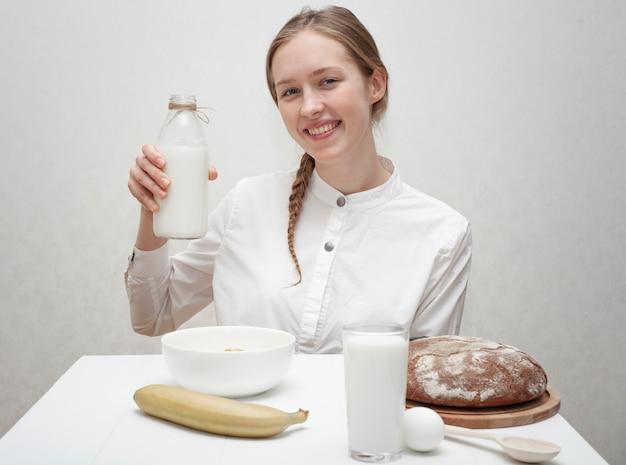 ミルクのボトルを保持しているスマイリーの女の子 無料写真
