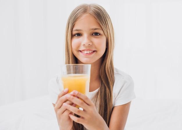 オレンジジュースのガラスを保持しているスマイリーの女の子 無料写真