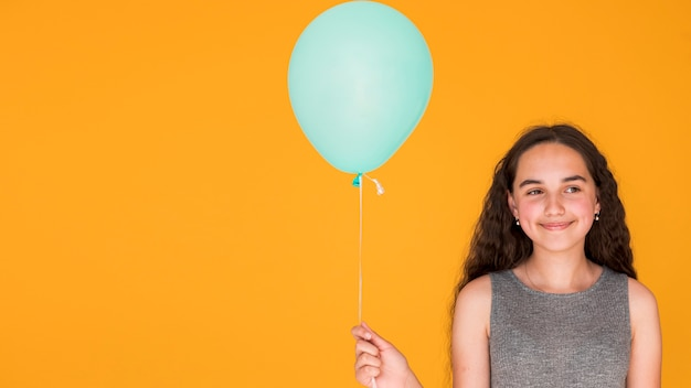 Smiley girl holding a blue balloon with copy space Free Photo