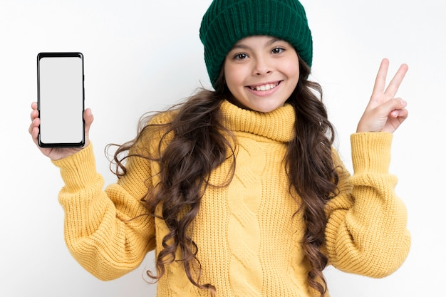 Smiley girl holding phone and showing peace sign Free Photo