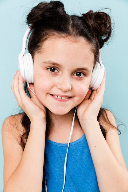 Smiley girl listening music at headphones Free Photo
